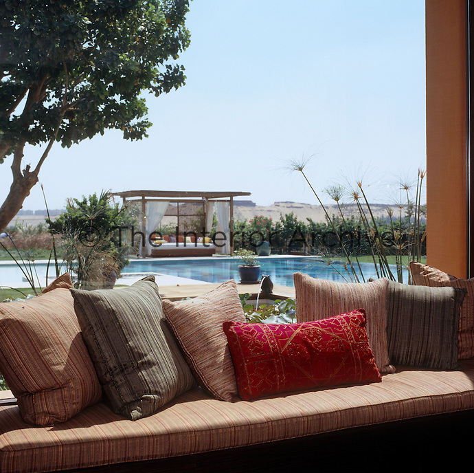 On the shady terrace a banquette piled with cushions overlooks the outdoor swimming pool