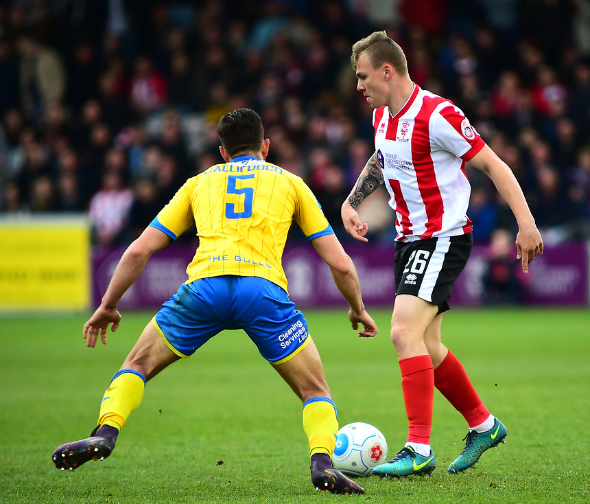 Lincoln City's Harry Anderson vies for possession with Torquay United's Giancarlo Gallifuoco<br /> <br /> Photographer Andrew Vaughan/CameraSport<br /> <br /> Vanarama National League - Lincoln City v Chester - Tuesday 11th April 2017 - Sincil Bank - Lincoln<br /> <br /> World Copyright &copy; 2017 CameraSport. All rights reserved. 43 Linden Ave. Countesthorpe. Leicester. England. LE8 5PG - Tel: +44 (0) 116 277 4147 - admin@camerasport.com - www.camerasport.com