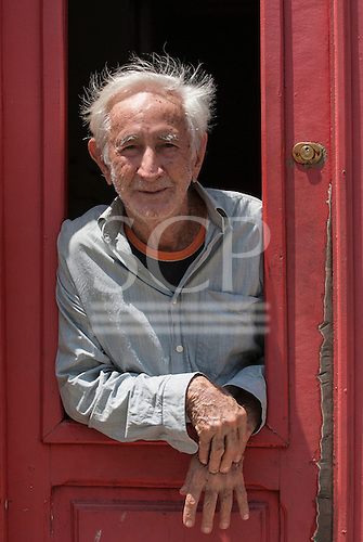 Olinda, Pernambuco State, Brazil. Old man looking out of red window in door of his colonial house.