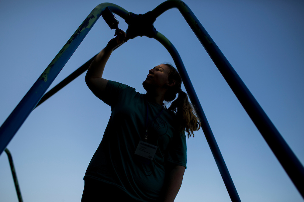"""Gracie Francisco paints a playground swing during """"Circle the City with Service,"""" the Kiwanis Circle K International's 2015 Large Scale Service Project, on Wednesday, June 24, 2015, at the Friendship Westside Center for Excellence in Indianapolis. (Photo by James Brosher)"""