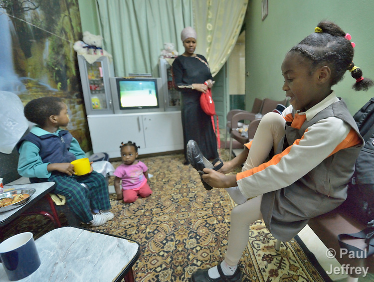 Dana Karim, a 7-year old refugee girl whose family came from the Darfur region of Sudan, puts on her shoes as she gets ready for school in the family's crowded apartment in Cairo, Egypt. Her parents both take adult education classes provided by St. Andrew's Refugee Services, which is supported by Church World Service. her mother and two siblings look on.