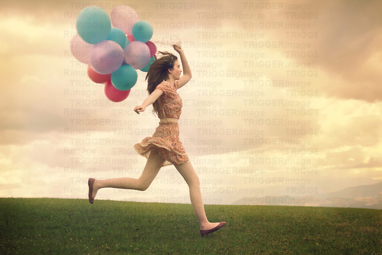 A young slim girl in a floral dress running on a field with colorful balloons