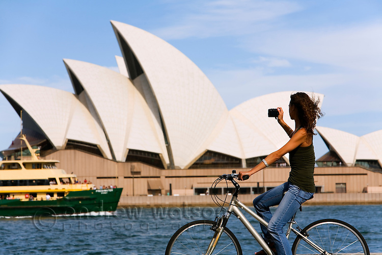 A woman cycling around Sydney harbour photographs the Opera House.  Sydney, New South Wales, AUSTRALIA.