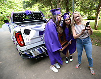 Claire Williams (from right) shows photographs that she took Thursday, May 14, 2020, to her daughter, Eliza Williams and her friend Sydney Kincaid before taking part in  a parade for 2020 Fayetteville High School graduates who attended or live in the Root Elementary School district. The parade wound through several neighborhoods around Root Elementary before ending at the school. Visit nwaonline.com/200515Daily/ for today's photo gallery.<br /> (NWA Democrat-Gazette/Andy Shupe)