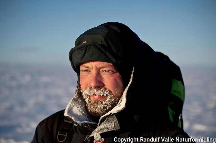 Mann med is i barten på Finnmarksvidda en februardag. ---- Man on Finnmarksvidda a cold winter day.