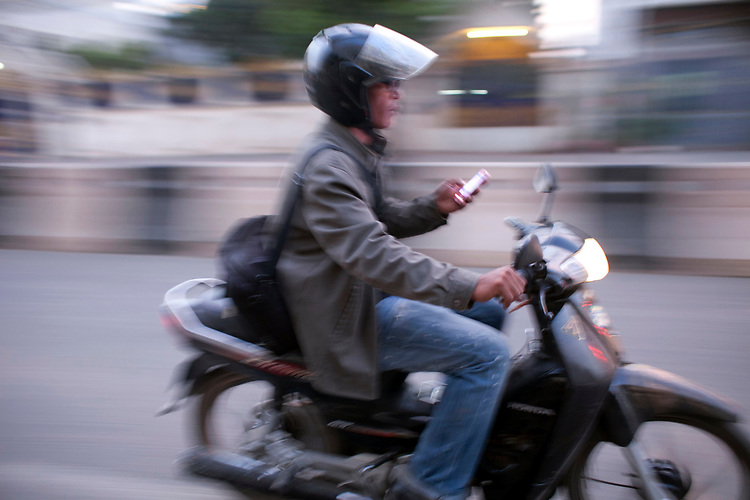 A motorcycle rider checks his smartphone in Phnom Penh, Cambodia. <br /> <br /> Photos &copy; Dennis Drenner 2013.