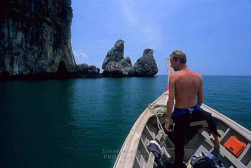 Man on bow of longtail boat preparing to anchor at scuba diving site, offshore, Railay Rei Lei Beach Thailand