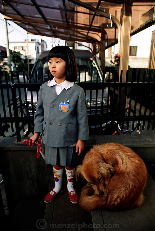 Maya Ukita, in kindergarten, uses her time before school to skip rope and play with the family dog. Japan. Published in Material World: A Global Family Portrait, page 55. The Ukita family lives in a 1421 square foot wooden frame house in a suburb northwest of Tokyo called Kodaira City.