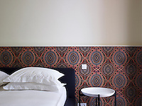 Patterned wallpaper by Eley Kishimoto highlights the wall of a guest bedroom