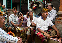 Bali, Indonesia.  Village Men Watching Re-enactment of a Traditional Balinese Hindu Story.  They are wearing the udeng, the traditional Balinese head cloth.
