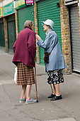 Two elderly women with walking sticks chat in Church Street, London.