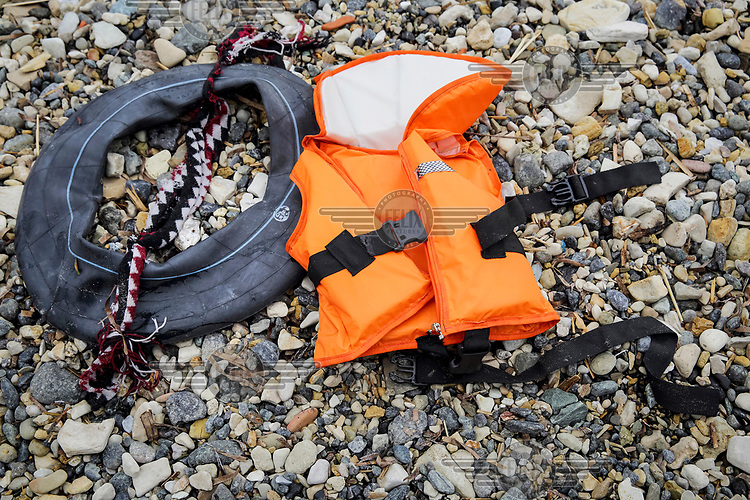 A life jacket and an inner-tube used as a life saver, abandoned on the shore.