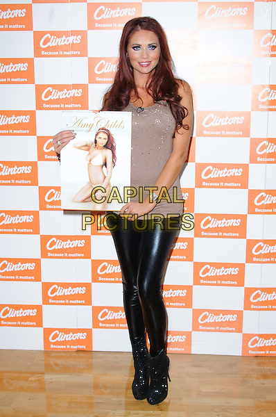 Amy Childs.Former TOWIE star meets the fans and signs copies of her Official 2012 Calendar at Clintons, Bluewater shopping center, Kent, England, .12th November 2012..full length  leather pvc shiny  brown beige  top t-shirt  ankle boots .CAP/CJ.©Chris Joseph/Capital Pictures.