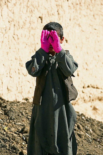 A boy in the village of Pir Zadeh, in Maiwand district, Kandahar province, Afghanistan, hides his face behind a pair of gloves given to him by a U.S. soldier. Troops from Company C, 2nd Battalion, 2nd Infantry Regiment were in the village to distribute winter clothing and food staples. They say such efforts help build rapport with villagers. Jan. 4, 2009. DREW BROWN/STARS AND STRIPES