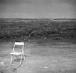 1979, Brigantine, NJ. Deserted chair along highway pull-off. File#79-251-6. 1/2.