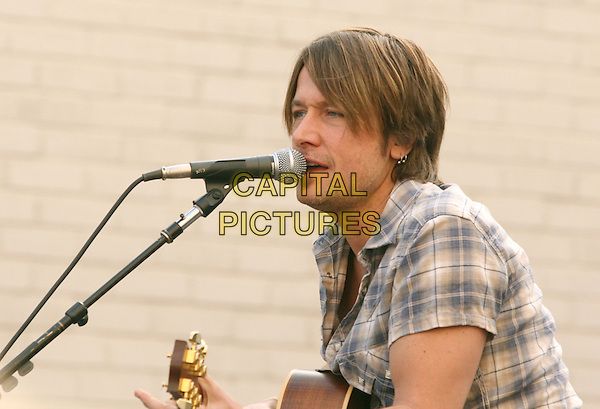 KEITH URBAN.is joined by Verizon Wireless and Samsung Mobile as he makes an in-store appearance for his fans at the Verizon Wireless store in Pasadena, California, USA, November 21st 2009                                                                   .half length music concert gig live on stage grey gray brown plaid checked check shirt microphone  tattoo bracelets singing profile guitar .CAP/RKE/DVS.©DVS/RockinExposures/Capital Pictures