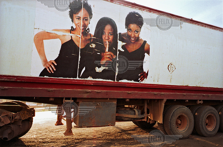 Advertisement on the side of a passing truck showing three young women.