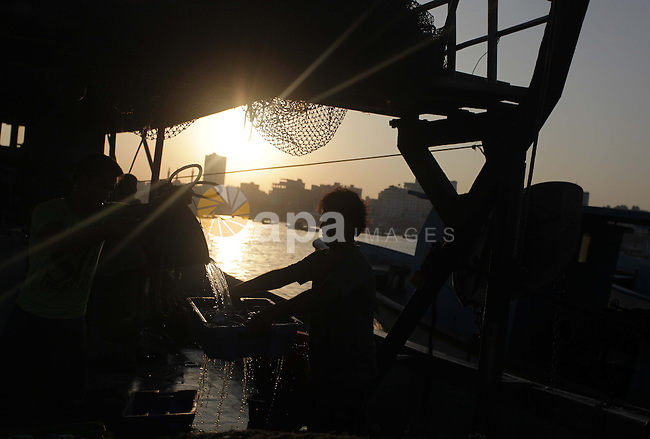 Palestinian fishermen work on their boat at the Gaza seaport in the west of Gaza City, 02 September 2013. The Egyptian navy boats attacked the Palestinian boats off the southern Gaza Strip last Friday, near the border with Egypt, wounding fishermen and the arrest of 5 fishermen. Photo by Ashraf Amra