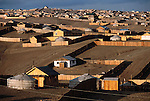 Gers and hand built homes without water or plumbing sprang up on the outskirts of Ulaanbaatar, Mongolia as more and more of Mongolia's rural population moved to the capital city to find work. (Gers are circular tent-like dwellings with a collapsible wooden frame covered in animal skins, felt, and/or canvas. It serves as a home for shepherds and families alike. Traditionally, the structures fit the lifestyle of the largely nomadic Mongols. As the population became more stationary, the ger continued to be used as animal skins and wool felt were, and are, easier to procure while more western style building materials were expensive and scarce.) From coverage of revisit to Material World Project family in Mongolia, 2001.
