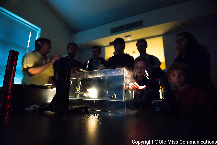Ukesh Koju, left, a ph.D. student in Physics, shows visitors what sound can do to water during the open house at the NCPA's 30th anniversary celebration. Sound can vaporize water as Colin Beach catches some in his hand. Photo by Kevin Bain/Ole Miss Communications