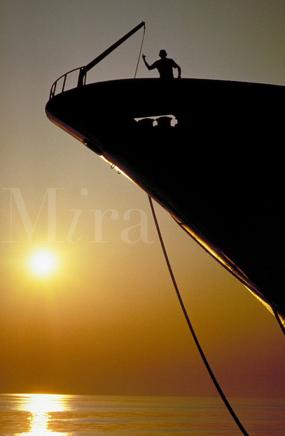 Silhouette of bow of ship at sunset with workmen on deck. Alabama.