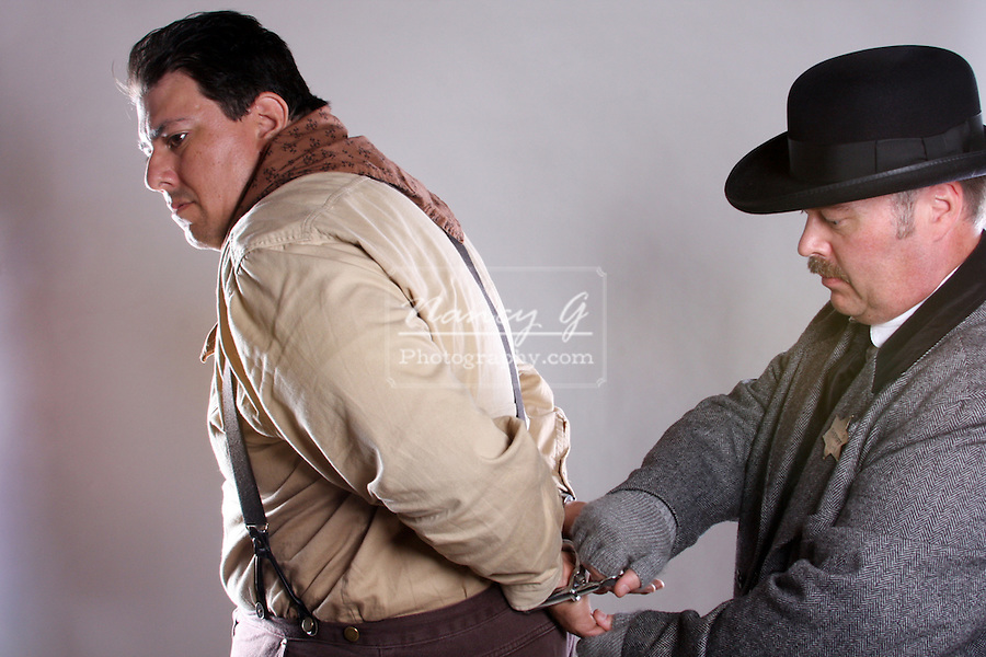 A old west sheriff putting handcuffs on a cowboy