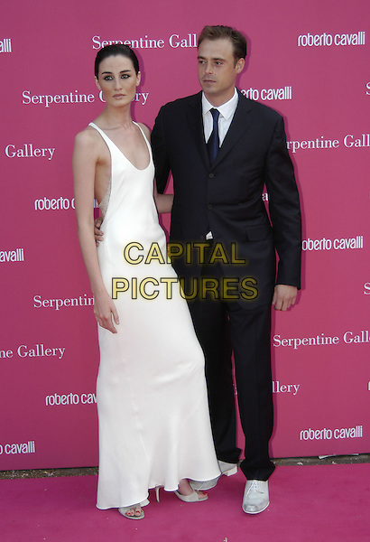 ERIN O'CONNOR & JAMIE THEAKSTON.Arrives at the Serpentine Gallery Summer Party,.Kensington Palace Gardens,.London, 16 June 2004..full length full-length long white dress suit white shoes celebrity couple.www.capitalpictures.com.sales@capitalpictures.com.©Capital Pictures