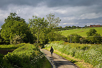 Women walks down a country lane, Oxfordshire, United Kingdom