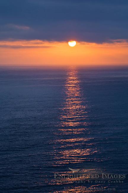 Golden orange sunset light reflected on ocean below dark clouds from Point Vicente, Palos Verdes Peninsula, California