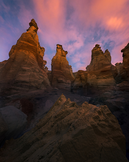 Sandstone pillars catch sunrise light, photographed deep within one of Arizona's canyons.