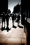 Silhouetted pedestians on city pavement