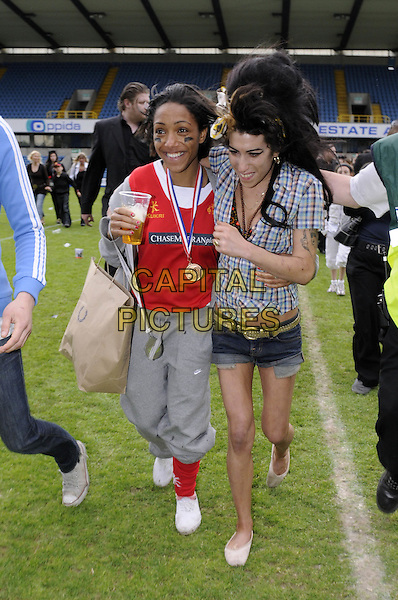 AMY WINEHOUSE.Arrives at the annual Soccer Six charity football match at Millwall Football Club, London, England, 18th May 2008..6 FC full length tartan plaid check blue shirt denim shorts hotpants pitch ballet shoes head scarf beehive brown paper bag .CAP/DH.©David Hitchens/Capital Pictures