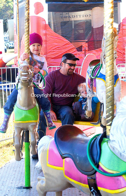 HARWINTON, CT.- 05 OCTOBER 2014 - 100514JW04 - Kaitlyn Almand age 4 enjoys a merry go round ride with her father David Almand of Harwinton and little brother Ben Almand age 2 Sunday morning during the Harwinton Fair.<br /> Jonathan Wilcox Republican-American