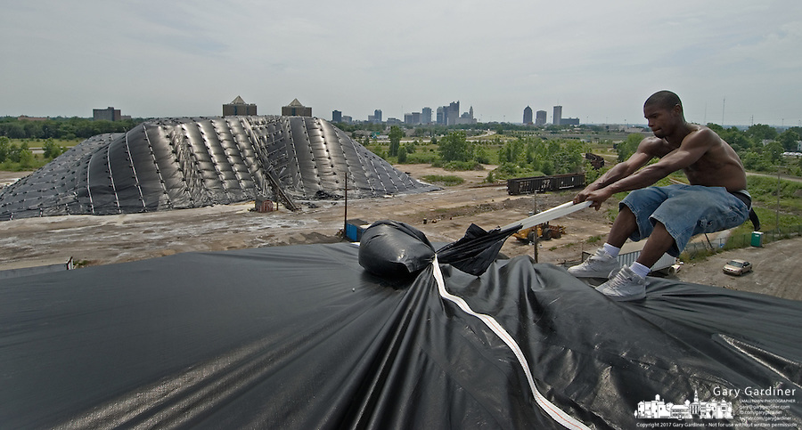 Jermaine Melvin leans over the edge of a Cargill Mining mound of salt to stretch a tarp tight across the top of the pile Sunday, June 25, 2006, in Columbus, Ohio. At left is another mound that was previously covered but was damaged in Thursday's wind storm and had to be repaired before completing the second mound along I-670 east of the city. (Photo by Gary Gardiner/EyePush Newsphotos)<br />