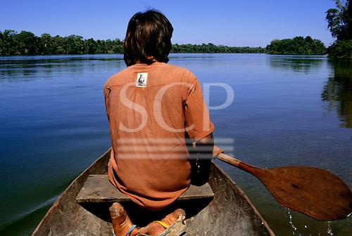 Mato Grosso State, Brazil; Gregorio, a Rikbaktsa Indian, paddling a canoe.