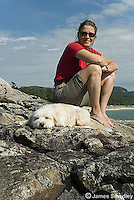 Woman sitting with her pet dog on a rock bluff
