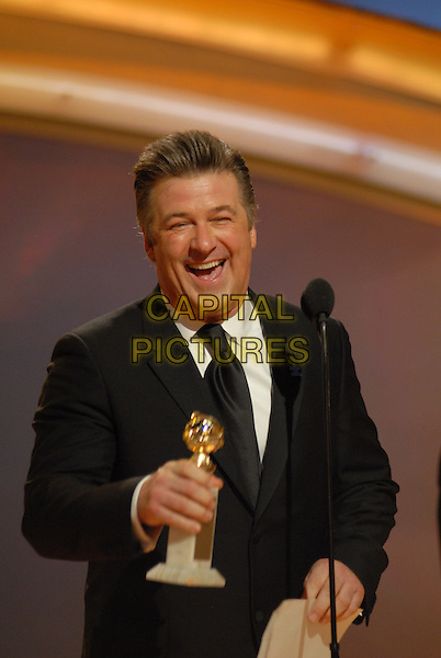 "ALEC BALDWIN.Accepts the award for Best Performance By An Actor In A Television Series ? Musical or Comedy for ""30 Rock"".Telecast - 64th Annual Golden Globe Awards, Beverly Hills HIlton, Beverly Hills, California, USA..January 15th 2007. .globes half length stage microphone trophy black suit jacket mouth open .CAP/AW.Please use accompanying story.Supplied by Capital Pictures.© HFPA"" and ""64th Golden Globe Awards"""