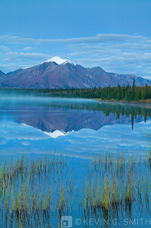 Mountain reflected  in Drasher Lake before dawn, Denali Highway, fall Alaska, USA