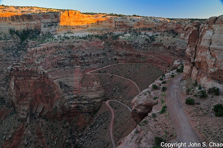 Sunset highlights Shafer Canyon rim above the steep switchback descent of rugged Shafer Canyon Trail dirt road, Island In The Sky, Canyonlands National Park, Utah.