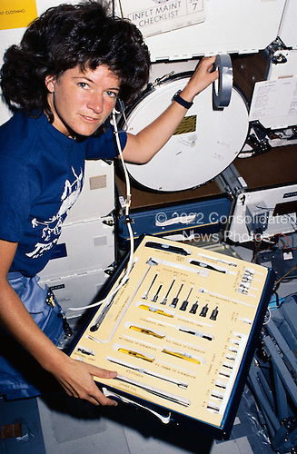 "Astronaut Sally K. Ride, STS-7 mission specialist, displays the array of tools at her disposal on the mid deck of the Earth-orbiting Space Shuttle Challenger during the STS-7 mission, June 18-24, 1983. Dr. Ride is positioned near the monodisperse latex reactor (MLR) experiment. They cylinder near her elbow is the actual reactor and the device next to it at right frame edge is the MRL apparatus container. Dr. Ride and four other astronauts are sharing duties aboard the reusable spacecraft for a six-day space mission full of ""firsts."" This photograph was made with a 35mm camera. It was among the visuals used by crewmembers at their post-flight press conference.  Dr. Ride passed away due to Pancreatic Cancer on Monday, July 23, 2012..Credit: NASA via CNP"