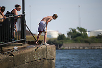 Saturday July 26th 2014 <br /> Pictured: Cardiff Bay <br /> RE: Boy looking over the edge about to jump into the water at Cardiff Bay during the heat wave