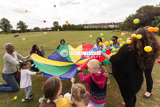Lordship Hub Co-Op Parents/Carers & Toddlers Group outing to Lordship Recreation Ground, London Borough of Haringey, North London UK, with volunteers & parents/carers - parachute game