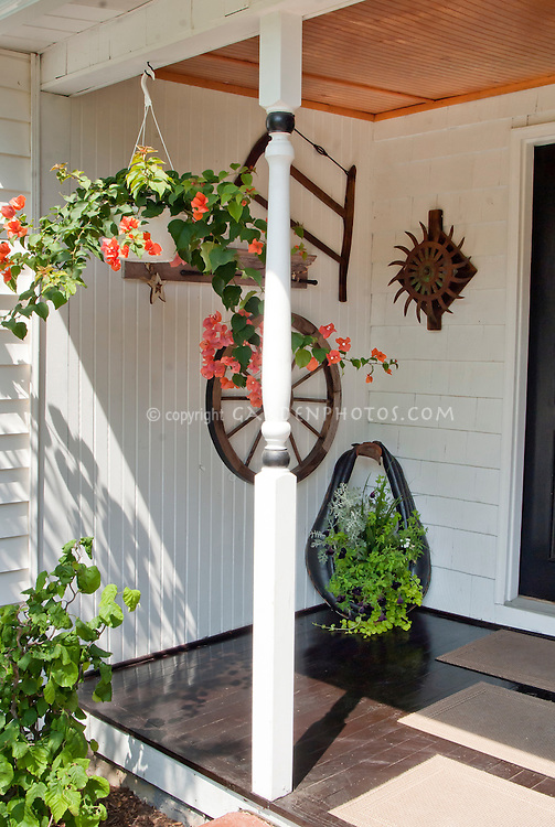 Front porch hanging basket and containers, with rustic farm tools, wagon wheels, antiques and flea market finds for cute curb appeal entryway