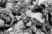 Goma, Zaire<br /> July 1994<br /> <br /> A pile of dead Hutu soldiers is carried off one by one to be buried after fleeing Rwanda. <br /> <br /> Following the 1994 Rwandan Genocide, in which Hutu militia groups and the Hutu lead Rwanda military, killed an estimated 800,000 ethnic Tutsis and sympathizers during a 100-day killing spree, 2 million ethnic Hutu&rsquo;s, fearing reprisals, flee the country. The vast majority went to Goma, Zaire as tens of thousands died in epidemics of cholera and dysentery that swept the roadside crowds and refugee camps. People who had actively participated in the genocide hid among the refugees, fueling the First and Second Congo Wars.<br /> <br /> The international community, and the United Nations in particular, drew severe criticism for its inaction in the wake of the Rwandan Genocide.