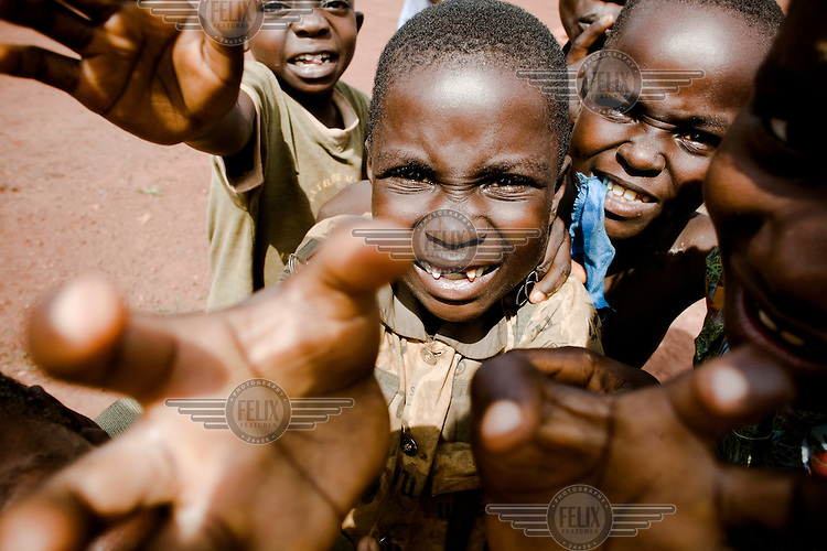 A young child with his front teeth missing, stands, arms outstreched, in a group of other smiling, orphaned children