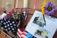 Phoenix, Arizona. July 3, 2013.  A small makeshift memorial for the 19 Arizona firefighters who died on June 30 battling the Yarnell Hill wildfire was built outside the Forensic Science Center in Phoenix, where autopsies are being conducted. A sign written by Captain Albert Bandin honors the 19 members of the Granite Mountain Hotshots team who perished fighting a wildfire in the community of Yarnell, Arizona. Photo by Eduardo Barraza © 2013
