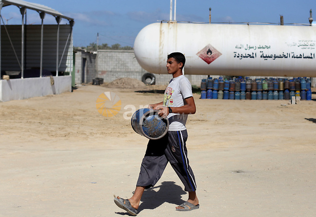 A Palestinian man carries a cooking gas canister after filling it, outside a gas filing station in Dir al-Balah in the central Gaza Strip September 17, 2013. The Gaza Strip is experiencing a shortage in cooking gas brought in from Israel, residents said. Photo by Ashraf Amra