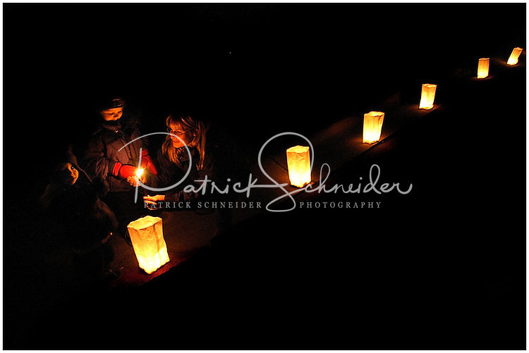 A family (mother and two sons) like luminaries along their driveway on a winter night. Photo taken near Charlotte, NC. Model released image.