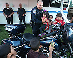 Nevada Highway Patrol Trooper Mike Ortega helps Lilah Torres, 3, check out his motorcycle during the 14th annual National Night Out in Carson City, Nev., on Tuesday, Aug. 2, 2016. <br />