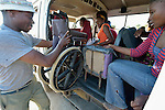 A man shoves a folded wheelchair into a kombi--a van used as public transportation--in Bulawayo, Zimbabwe. The wheelchair belongs to Delina Nleya. She and other people in wheelchairs in Zimbabwe are often ignored by kombi drivers, or they're charged double to bring their wheelchair along. Nleya suffered a spinal cord injury and uses a wheelchair provided by the Jairos Jiri Association with support from CBM-US.